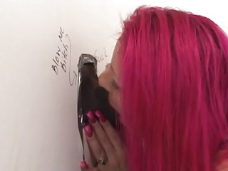Pink haired Milf sucking big black cock at the gloryhole
